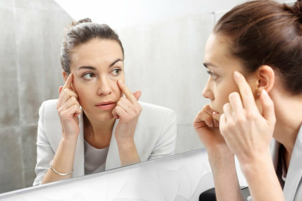 Woman Examines Visible Signs of Stress in the Mirror and Considers Cosmetic Procedures as a Solution