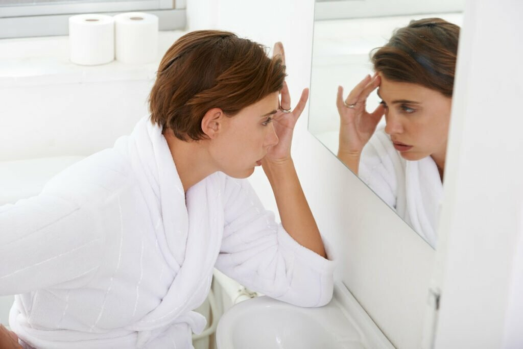 Tired Woman Looking in Mirror Wanting to Refresh Appearance Post-Pandemic with Non-Surgical Facial Procedures